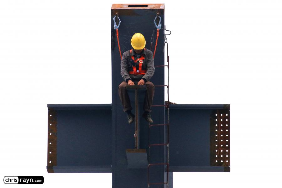 Construction worker chained high up to massive steel column