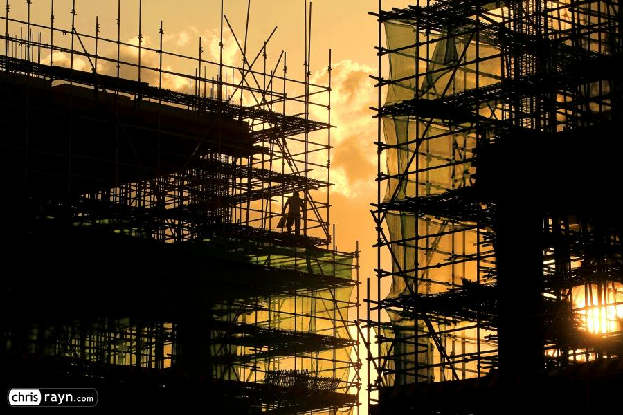 A Worker leaving the steel frame construction at sunset