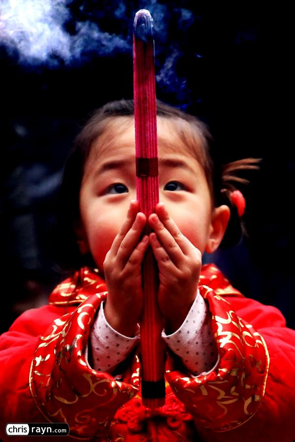 A Chinese praying girl, looking up to her future