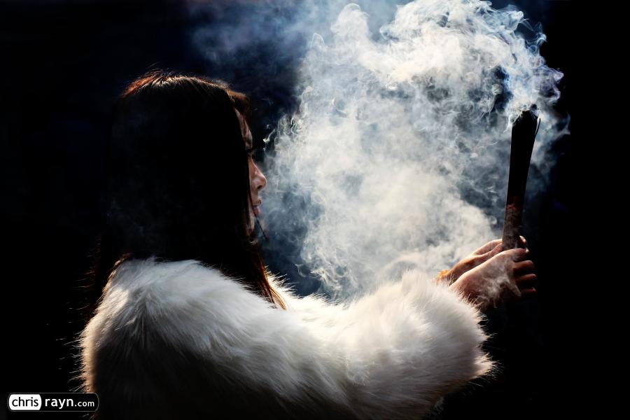 A young woman clad in white fur, and white incense smoke