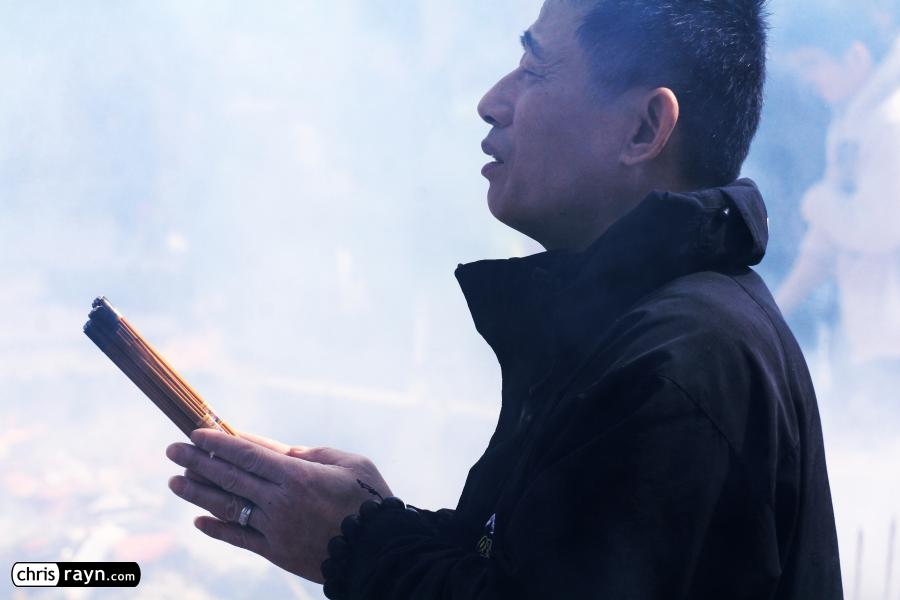 A praying man in front of a wall of smoke in the temple