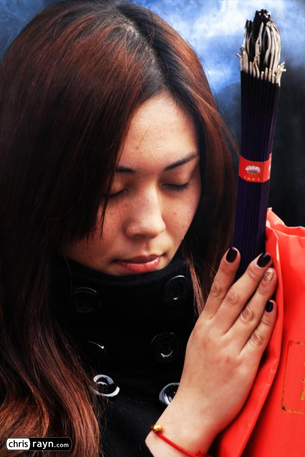 Well-protected from the cold, a young woman in deep prayer