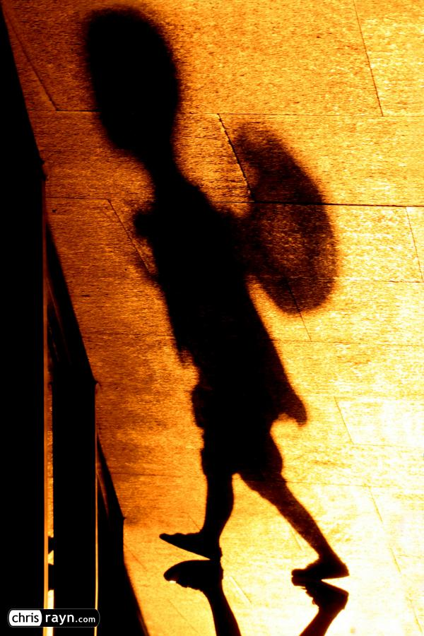 In shadows, a boy with hat is wandering