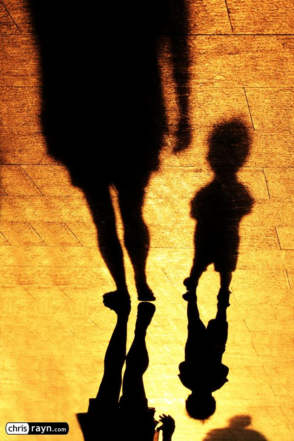 Shadows of a toddler, walking with his mother