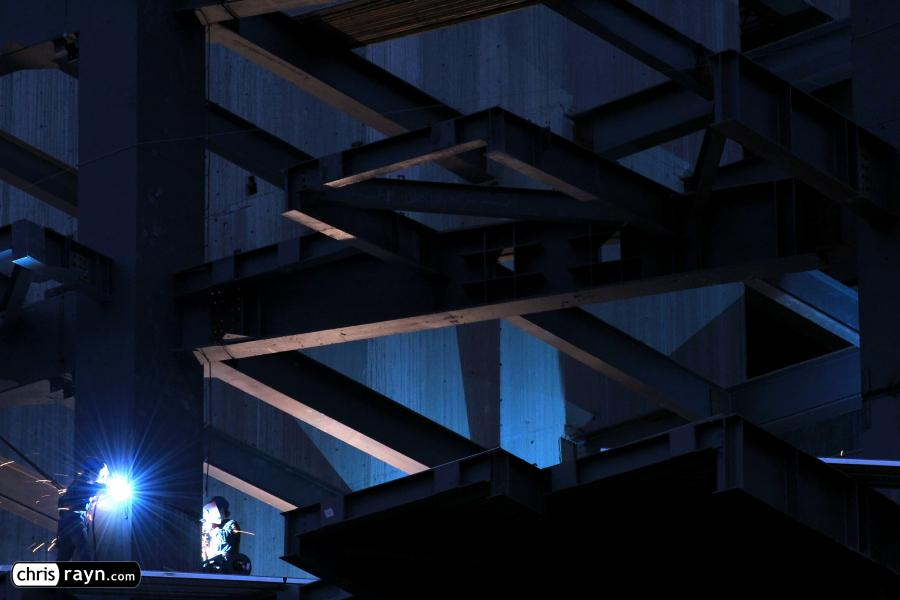 Welders light up a construction site at night