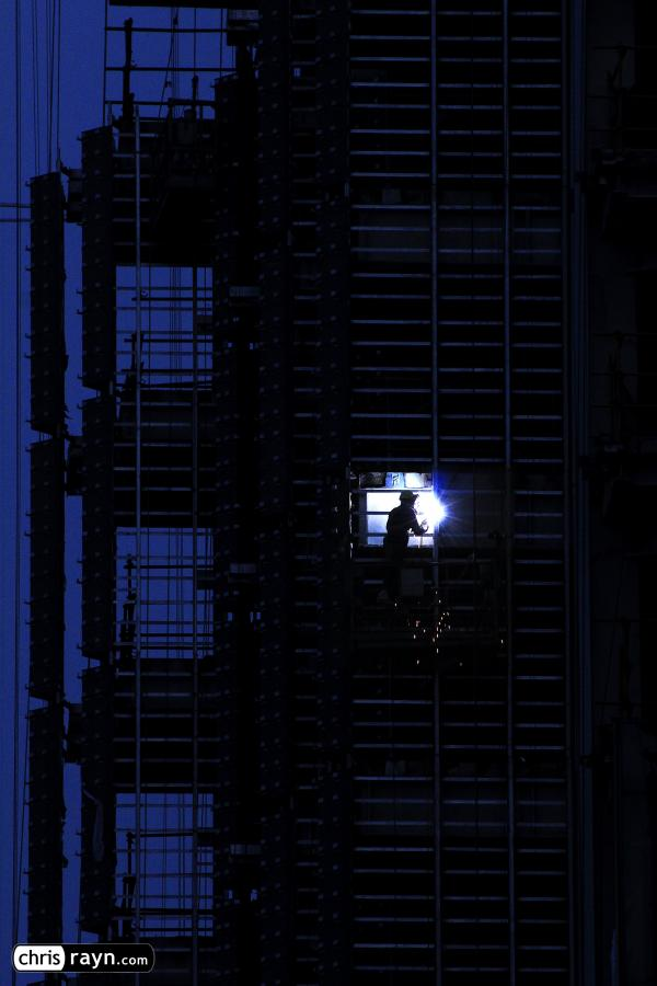 A lone welder illuminates a skyscraper at night