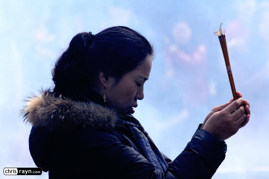 A praying woman in front of a wall of smoke in the temple