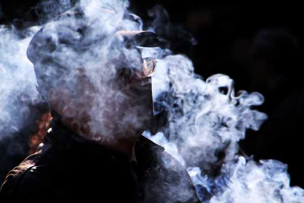 Smoke billows around a spectacled man in the Chinese temple