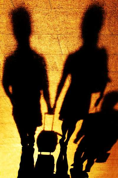 A couple carries luggage together, their shadows in cooperat