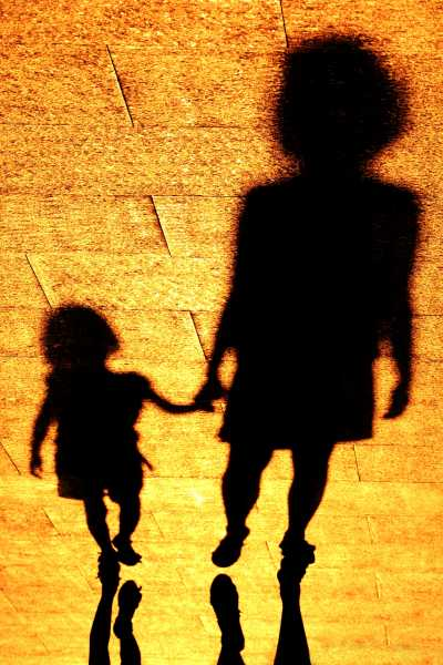 In shadows, a girl is looking up to her mother