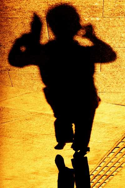 A preoccupied shadow is juggling a phone and tablet