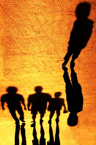 In shadows, a toddler stands seperated from his family