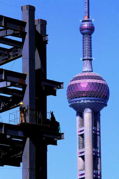Welding a new high rise in front of Oriental Pearl Tower