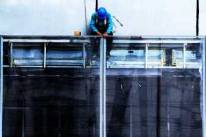 Construction worker on top of a giant glass door